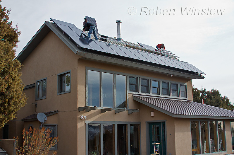 Model Released, Workers installing Schuco 180 W, model MPE 18- MS 05 Photovoltaic Panels on a South Facing Roof, Hose is also Passive Solar,  Durango, Colorado, USA, North America