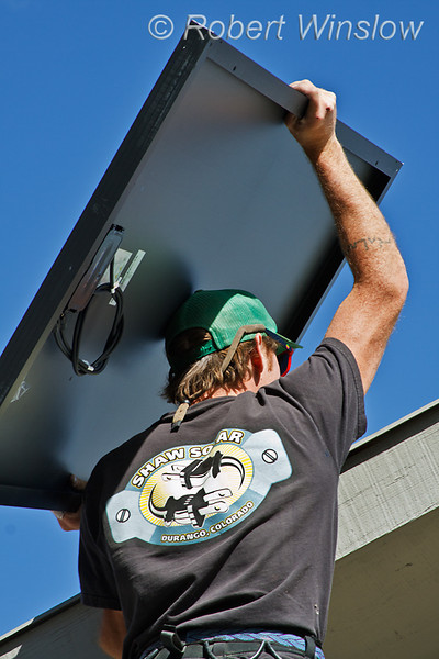 Model Released, Technician worker lifting photovoltaic solar panel onto roof for installation, Durango, Colorado, USA, North America