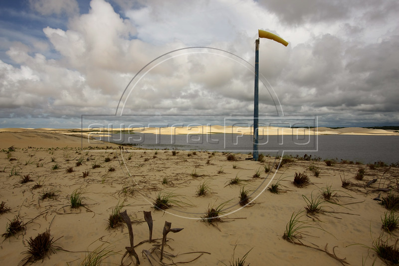 A wind sock shows the wind direction on sand dunes planted with local vegetation to control their spread in Luis Correa, Piaui state Brazil. While the magnificent dunes of Brazil's northeast are a natural occurance, in some places a perfect storm of factors, including unchecked human impact on the land, has lead to what amounts to a tropical version of a glacier. Powered by the wind, the dunes advance a few meters per year, overtaking anything in it's path. In the town of Ilha Grande, an entire neighborhood is underneath the sand. Experts say the sand may even block the Parnaiba River from reaching the ocean, which would have far-reaching environmental and social repercussions. (Australfoto/Douglas Engle)