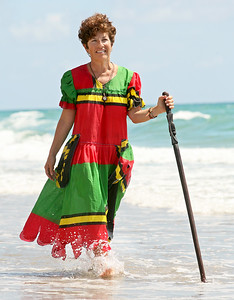 072411 - HIGHLAND BEACH - MEET YOUR NEIGHBOR - Karen Robinson walks Highland Beach, wearing a dress and using a hand-carved walking stick that were given as gifts to her by her sister family while serving in the Peace Corps in Vanuatu.  The dress symbolizes the flag of Vanuatu.  Photo by Tim Stepien