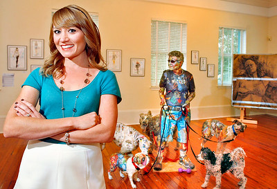 "111914 - DELRAY - Melanie Johanson, Curator at Cornell Museum of Art at the Delray Beach Center for the Arts, pictured Monday morning at the Cornell Museum with one of artist Will Kurtz's newspaper sculptures, ""Linda the Dog Walker"".  Photo by Tim Stepien"