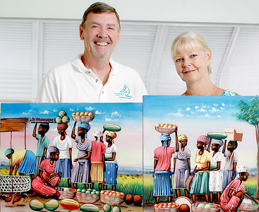 031816 - BRINY BREEZES - Ken and Sue Gross show off a few of their faviorite Haitin paintings Friday morning inside of their Briny Breezes trailer. Ken and Sue started the mission society and have been going to Haiti for 15 years. They take teams to different areas that need projects done that the team is willing to work on. They take medical teams, do eyeglass clinics, built a school with construction teams from the States and are helping to build a guest house now in Port au Prince. They have also taken the children living in the tent cities and done play days and craft projects with them. Fund raisin during the year to support an orphanage in Jeremie and feed 200 children in a school in Dame Marie 1 meal a day of beans and rice. Sue took 3 teams last year and is heading to St Marc area with a team from MN on Feb 13th. Photo Tim Stepien