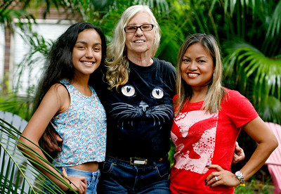 061616 - Lake Worth - Ulla Oest, center,  pictured with her adopted daughter Benilda Milrad, right and Benilda's daghter Ariel, left at God's Creatures Great and Small Sanctuary  in rural Lake Worth Thursday morning. In 1989, Ulla and her husband adopted a 10-year-old orphan from the Philippines, Benilda Milrad. Benilda is now married and lives in Coral Springs with her family.  Photo by Tim Stepien