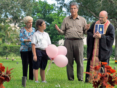 092815 - BOCA RATON - (L to R)  Bess Hatsis,  Ellie Ana Sperantsas,  Dean Sperantsas and Father Mark of St. Mark's Church in Boca Raton pray over the grave of Athena Sperantsas Monday afternoon at Boca Cemetery. They traditionally release balloons into the sky to honor Athena around her birthday, September 30th. Athena is the Mother of Dean, Grandmother of Ellie Ana, Friend of Bess Hatsis.   Photo by Tim Stepien