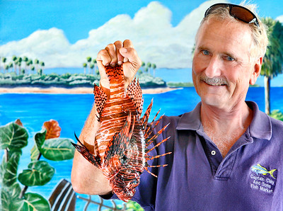 081616 - DELRAY -  Captain Clay Brand of Capt. Clay & Sons Seafood Market pictured Tuesday morning holding a lionfish that he speared off of Ft. Pierce. Captain Clay harvests a variety of the seafood for his market, including lionfish.  Photo by Tim Stepien