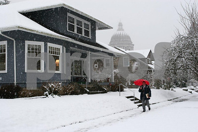 A man holding a red umbrella braves the snow in the historic section of Olympia, south of the Capitol.