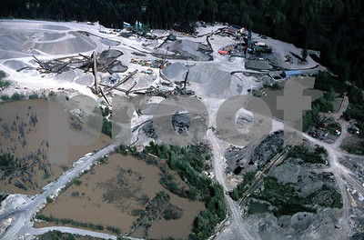 A gravel mine adjacent to a river creating runoff and water quality issues.