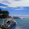 Boats that have been pulled off of their moorings lie stranded on the shoreline after seasonal winter storms in Hawaii