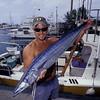 Boat captain Mike Milligan shows of fresh catch of wahoo or 'ono' (H), Acanthocybium solandri , Honokohau, Hawaii (Central Pacific Ocean)