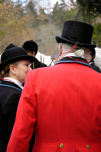 Back of man and woman fox hunters walking away from  the annual Blessing of the Hounds event at the Iroquois Hunt Club in Lexington, Kentucky, USA