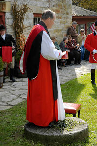 Minister speaking at the the Blessing of the Hounds event at the Iroquios Hunt Club in Lexington, Kentucky USA. The event marks the beginning of the hunting season and follows the tradition of honoring Saint Hubert, the patron saint of hunters. The minister  is standing one of the an old millstones from Grimes Mill on Boone's Creek..