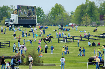 Stock image of horse and rider cross country international competitors and spectators at the Rolex Kentucky Three Day Event at the Kentucky Horse Park in Lexington, Kentucky, USA.  In this  image the horse and rider in the race also appear in the large television spectator viewing screen.