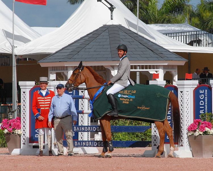 WEST PALM BEACH, FLORIDA - March 30, 2018: Francisco Jose Mesquita Musa and Sharapove Imperio Egipicia accepting the blue a ribbon at week 12 of the Winter Equestrian Festival in Wellington, Florida