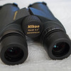 Tonji's Binoculars: Nikon Monarch 10x42<br /> <br /> Binoculars a birders most important tool. <br /> <br /> My current bins are the Nikon Monarch 10x42 DCF. The number 10 is the amount of magnification. So for this pair you see as if you are 10 times nearer the object. The second number in this case 42 is the objective diameter of the binoculars. The higher the number the brighter the image. I used to use the Nikon 8x42 bins. When they were accidentally dropped into the ocean I decided to get the same brand but I thought 10 x42 might be more useful. I think I do prefer the higher magnification. I find that bins with the objective diameter of 50 are too large. I think 42 is just the right size and weight for something that will be around my neck the whole day.<br /> <br /> Magnification is usually a personal choice. The two most common are 8x and 10x. A magnification of 8x gives you a bigger view while a 10x magnification makes the bird a little bigger. It is best to try both before buying to see which one suits you. I like 10x and Sylvia likes 8x. <br /> <br /> The specs of the Nikon  Monarch 10x42 binoculars are as follows:<br /> Magnification: 10<br /> Effective diameter (mm): 42<br /> Angular field of view: 5.5 degrees<br /> minimum focusing distance: 2.5 meters<br /> weight: 620 grams<br /> <br /> When I took this picture my bins were really dirty. We had just come home from a rugged week long trip. I fell from a horse, twice.  I slipped on the mountain trail a few times. There was a lot of dust. And there was one time when a whole dust cloud of orange spores covered me. My hair was orange. I guess it can be seen here that I had not cleaned my bins very well yet. <br /> <br /> The reason I am not so finicky with my bins is because I decided to go for the very reasonably priced Nikon Monarchs. This pair with the 10x42 magnification costs less than $300. They are light, clear and they work well. I usually strap them to my harness. Or they are in my car ready to look at any interesting birds. Bins live a hard life and I would rather get something that performs well but does not cost too much. <br /> <br /> There are nicer bins, the Swarovski EL 10x42 is superb. I tried a pair of Swarovski bins and I must say they are much better than my Nikon. The Swaros were a pleasure to use, brighter, sharper and gave me less eye strain. It was like watching TV, not looking thru bins. The cost is much more than my Nikon bins.  I like the Swaros a lot, but not the price. <br /> <br /> A weakness of the Nikons are the covers. They are pretty horrible. Easy to lose. I actually just lost the front covers already. Another problem is the eye cups can get damaged and stop moving. It is disappointing. The overall construction is ok. But as I do more birding and subject it to more use it does not seem to be holding up very well. These bins are ok I guess but if you want something that will last for a long time you need to look at some of the more expensive binoculars.<br /> <br /> I will probably upgrade to better binoculars at some point in time.