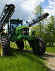 Deere sprayer coming out of a field