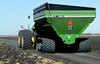 Brent 1084 grain cart on rubber tracks, being towed by John Deere tractor
