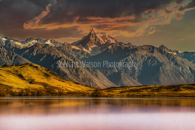 Sunset skies above the Southern alps reflected on LakeClearwater  in the Ashburton High country lake