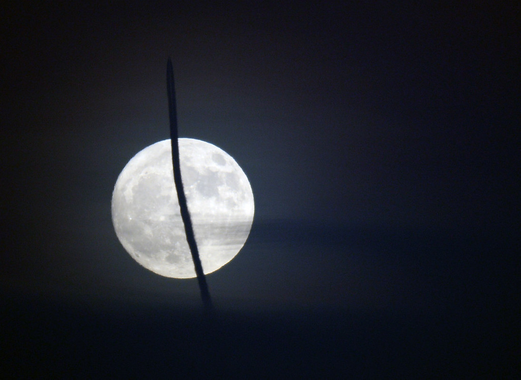 . A Super Moon rising with a jet chemtrail at the Air Force Academy.  Cliff Grassmick / Staff Photographer/ December 2, 2017, 2017