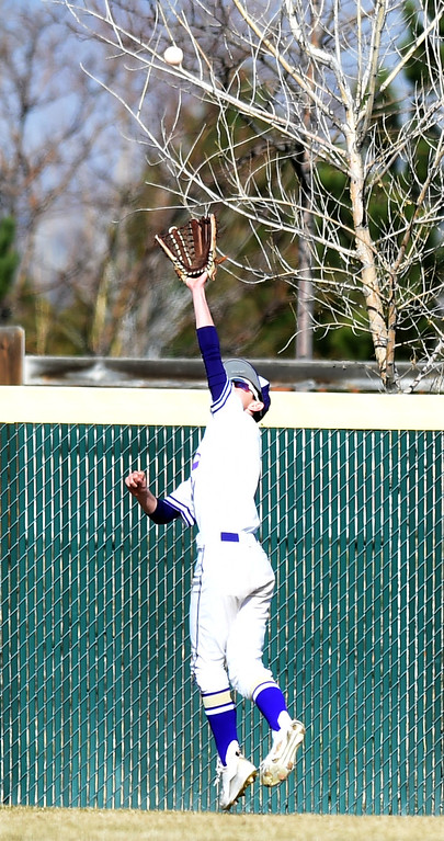 . Davis Martinek, of Holy Family, goes up to get a fly ball near the fence against Erie during the game at Holy Family in Broomfield on Saturday. For more photos, go to www.BoCoPreps.com Cliff Grassmick  Staff Photographer March 18, 2017