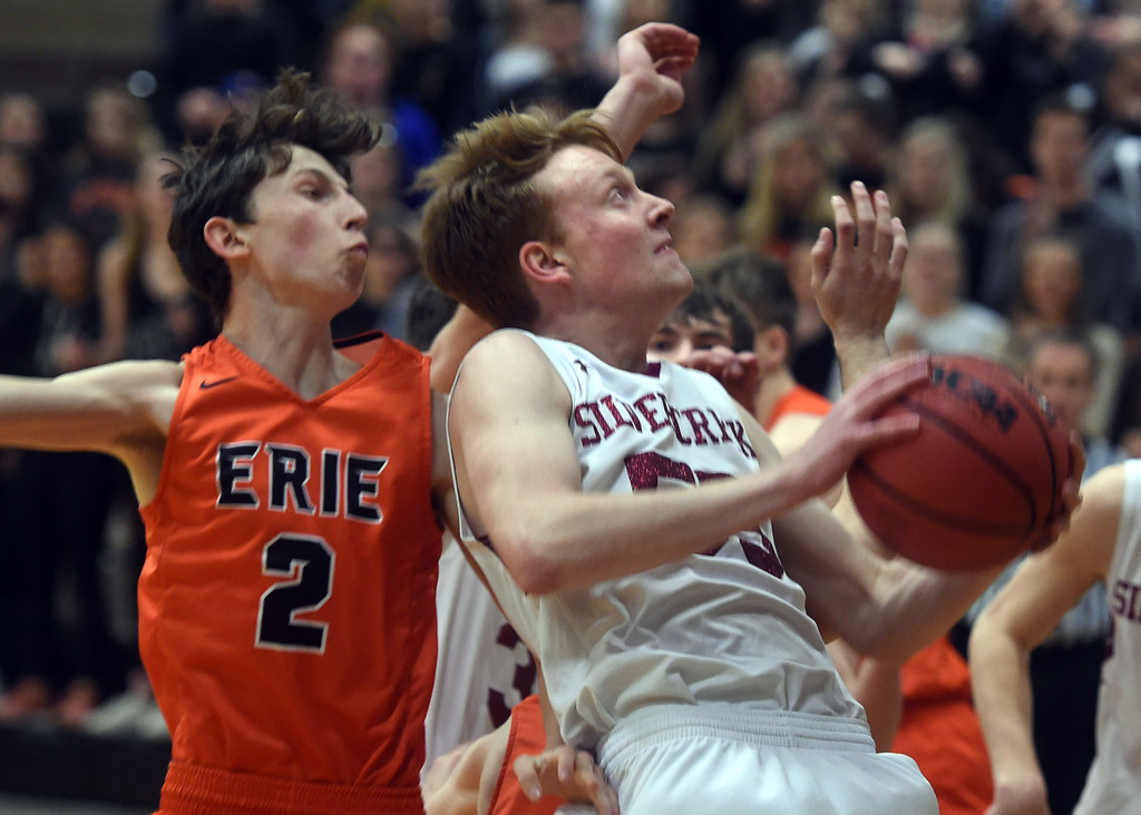 . Erik Grossaint, of Silver Creek, drives past Tyler Larson, of Erie. For more photos, go to BoCoPreps.com.  Cliff Grassmick / Staff Photographer/ February 24, 2018