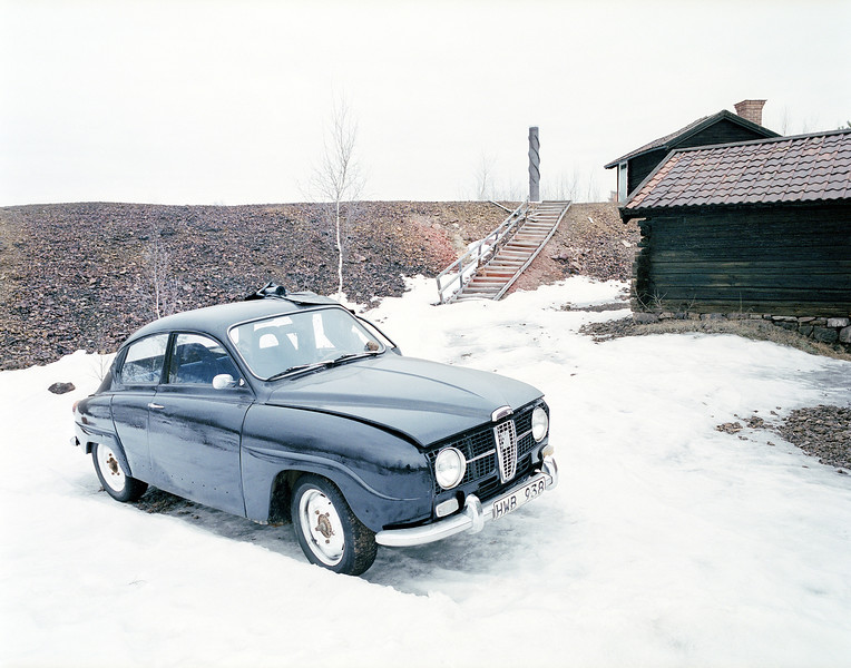 "AN OLD SWEDISH CAR ""SAAB"" SOROUNDED BY ONE OF THE OLD 1600 CENSORY BUILDINGS AND THE A LITTLE MOUNTAIN OF WAST FROM THE COPPER INDUSTRY IN FALUN. THE HOUSES IS STILL USED FOR HOUSING OF PEOPLE."