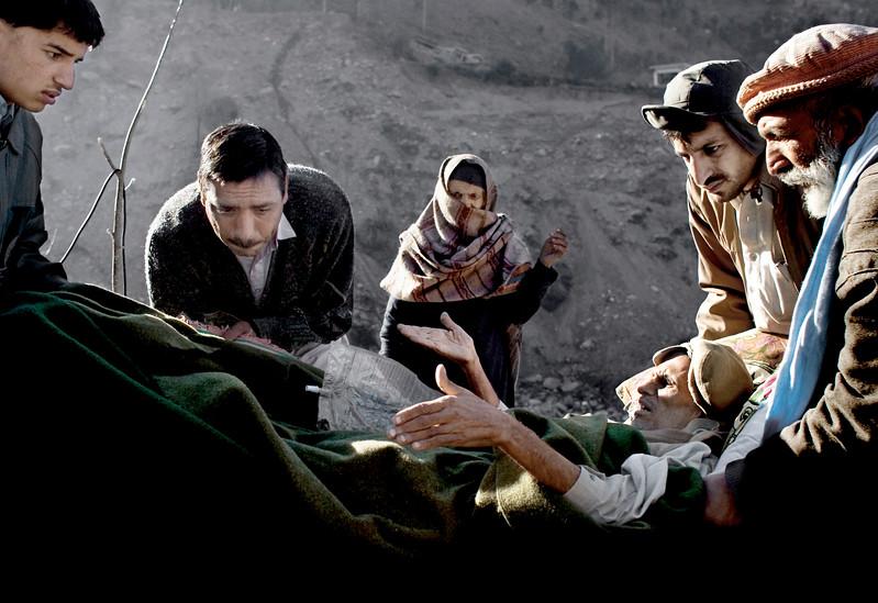 7:8 Dec 2005 Jordskælv i Pakisatn. Mand med liggesår bliver båret til Røde Kors klinik i Patika, Kashmir. Han blev senere evakueret i Muzaffrabad, da sårene var så dybe og inficeret.