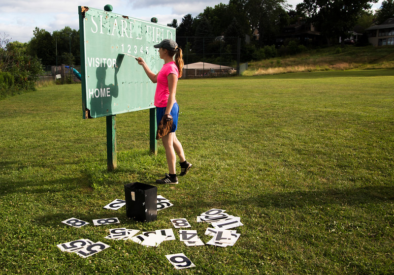 "Jackie Dresser hangs up the score after her team ""The Hot Chauts"" scored 6 runs during the first inning of their game with ""The Moms"" at Sharpe Field on Tuesday, July 25, 2017. ERIN CLARK / STAFF PHOTOGRAPHER"
