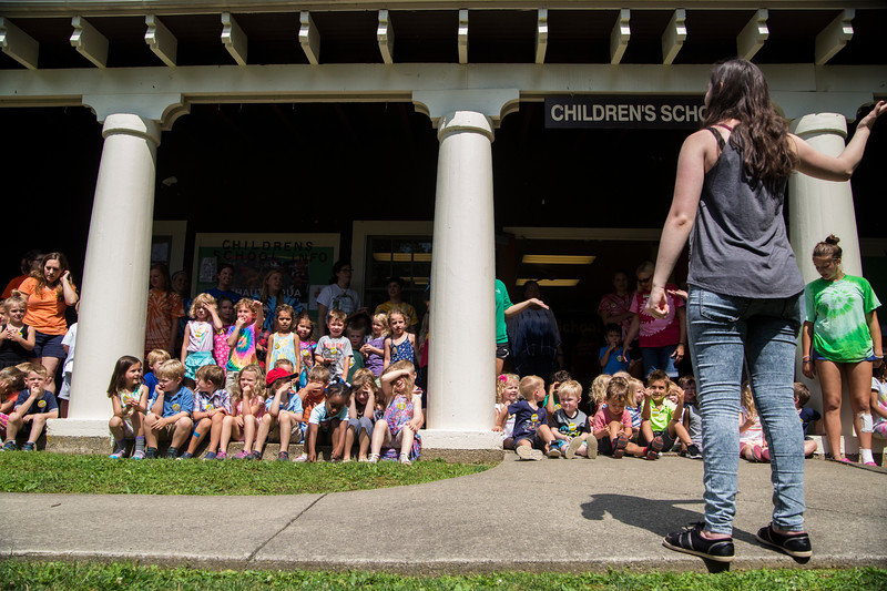 Children gather on the porch of the Children's School to sing songs for the open house on Friday, July 14, 2017. ERIN CLARK / STAFF PHOTOGRAPHER