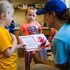 Elsie, left, and Lily, center, show their mom, Betsy Burgeson, crafts that they have made at the Children's School open house on Friday, July 14, 2017. ERIN CLARK / STAFF PHOTOGRAPHER