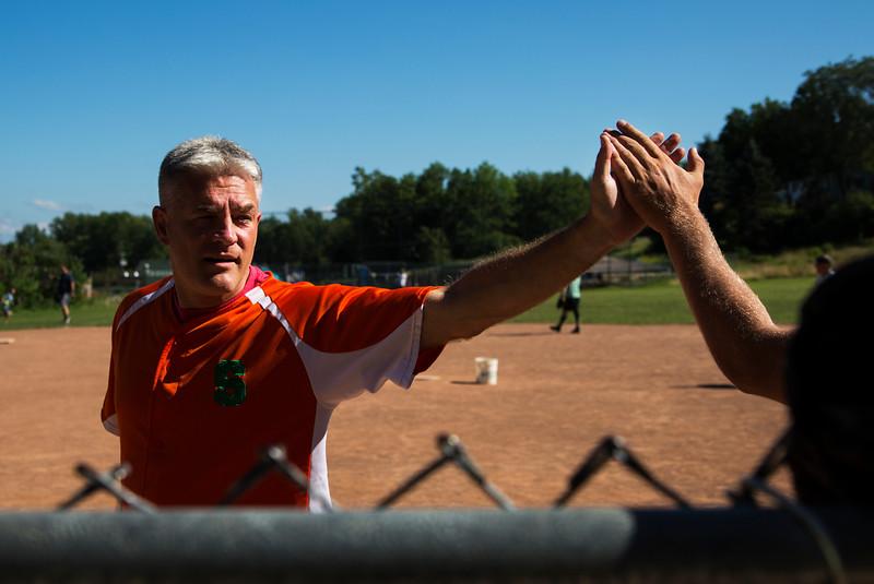 John Chubb high fives a team member after scoring a run during the Slugs softball game on Monday, July 17, 2017. ERIN CLARK / STAFF PHOTOGRAPHER