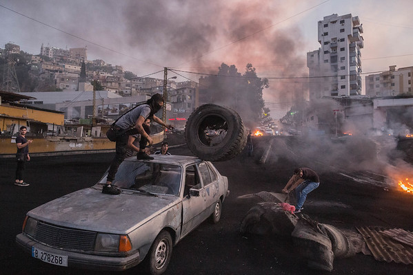 BEIRUT - 18 OCTOBER 2019: Protestors unload tyres from a car which they'll burn to block a highway in Beirut, Lebanon during unrest sparked by economic difficulties. <br /> <br /> Streets were blocked en-masse across Lebanon as the country woke up to the second day of what would become a wave of popular unrest against the Lebanese state.