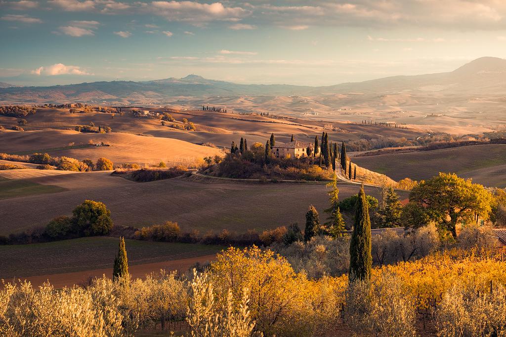 Idyllisches Anwesen  auf einem Hügel in der Toskana, Val d´Orcia, mit Zypressen in goldenem Licht im Herbst