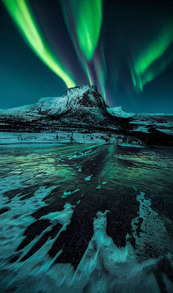 Magisches Polarlichtspiel mit eisigem Vordergrund in Nord Norwegen am markanten Granitberg Hjoerna