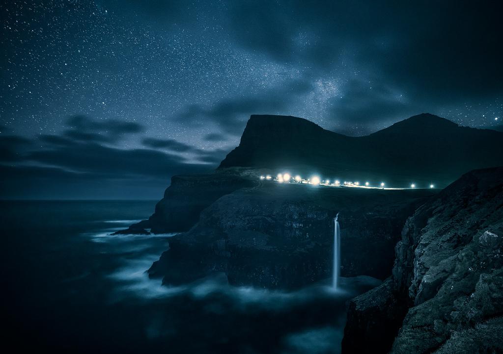 Der Wasserfall Mulafossur auf der Insel Vagar auf den Färöer Inseln bei Nacht mit Sternenhimmel