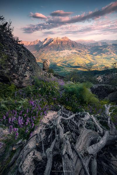 Blick vom Monte Ortobene auf die Gipfel Monte Corrasi und Punta sos Nidos mit der Stadt Oliena zum Sonnenuntergang mit prachtvollem Vordergrund