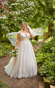 Soft and sweet, this plus size off-the-shoulder lace and tulle ballgown is designed for the bride who is dreaming and romantic at heart. This ultra-feminine, princess-inspired plus size ballgown is bedecked in French laces that really pop against the colored lining, and create a unique, natural texture in how they increase in thickness. The off-the-shoulder lace straps are highlighted with a narrowed plunging neckline, highlighting the upper body in all the right places! The bodice on this plus size wedding dress also features a high back for supportive construction and finished with fabric-covered buttons. A slight train completes this traditional ballgown silhouette for a delicate finish. This gown is also available in plus sizes.