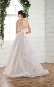 The trend-worthy ballgown of your dreams, this sparkling wedding dress is truly show-stopping! A classic V-neckline follows into organic lace straps for a touch of natural elegance, while a sequin layer is added to the bodice to highlight the sparkling beadwork for a textural shine. Floral laces are placed over the sequin and glitter tulle fabrics in the tiered skirt for a rich look that is light to the touch. The short train maintains the volume in this lively silhouette, which zips beneath fabric-covered buttons for a classic bridal touch.