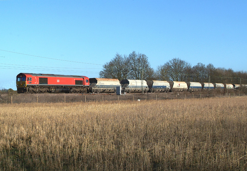 """So, after a false start with """" Maritime One """", the first sunny pictures of the year did arrive at last some 2 weeks later on 17th January 2018.<br /> 66185 Terling Rd. 09.59hrs. 6O79 09.45 Marks Tey Tarmac-Crawley New Yard RMC.<br /> NB Although originally booked to Crawley it ran only to """"Wembley Euro Frt Ops Centre """" at the request of the customer """".<br /> Very windy weather conditions today so no standing out in the Fens or at the Coast. <br /> Terling Rd. only...location of last resort."""
