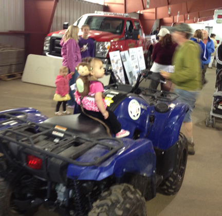 A young rider and companion enjoy a seat on a four-wheeler at the May 18 Estes Park Safety Expo at the Stanley Fairgrounds.