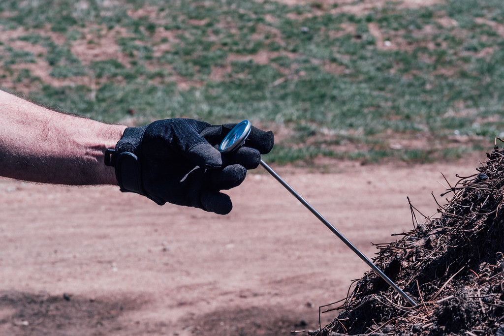 . Golf Course equipment manager Joseph Lingenfelter measures the temperature of a compost pile (Trail-Gazette)