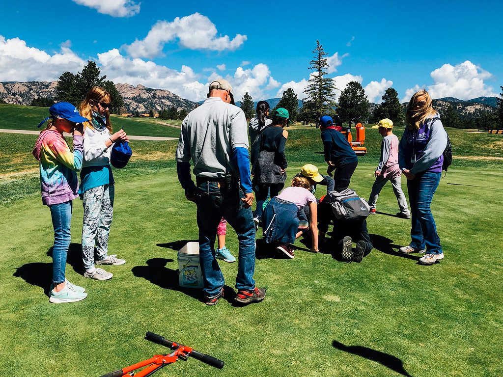 . Students learn how to move a hole on a putting green (Trail-Gazette)