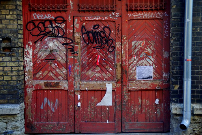 Graffiti on a red door in Tallinn, Estonia.