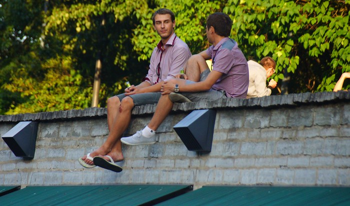 Young people drinking beer on a roof overlooking one of Tallinn's busier streets.