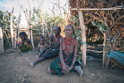 Dasanesh woman with children in front of his hut. Omorate, Omo Valley, Ethiopia