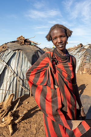 Dasanesh woman resting in shadow of hut, Omorate, Omo Valley, Ethiopia