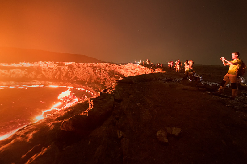 Tourists take photos at the rim of the volcano
