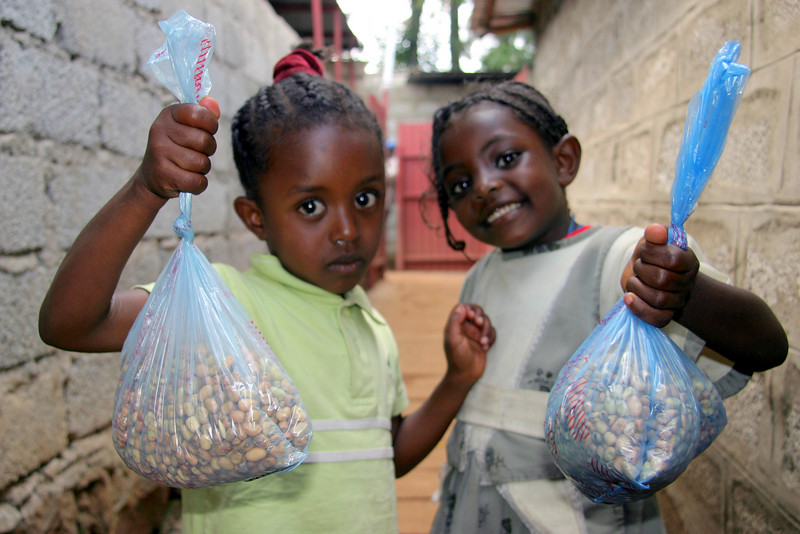 Two Beta Israel children leaving the Under Six Feeding Center with beans to take home. The children each receive 2 pounds (900 grams)  of food to take home and share with their families if they show up twice a day for meals on the NACOEJ compound in Addis Ababa or Chichila, Gondar