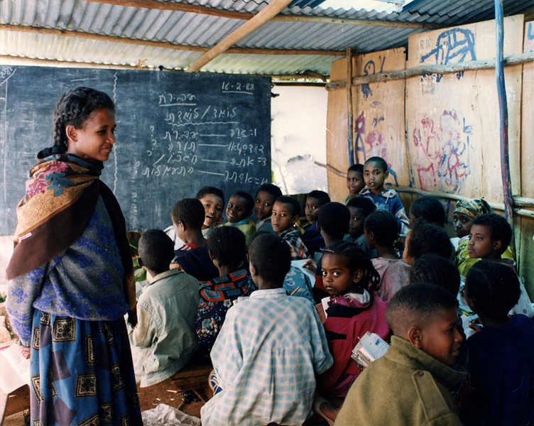 For many years the Beta Israel School did not have proper classrooms, rather they were structures made of plywood and corogated iron. The children did not have desks and sat on long benches. Money was needed for food and desks and proper classrooms had to wait. This picture shows the Ethiopian Jewish Students with their teacher in Hebrew class.