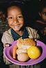 Ethiopian Jewish Child with school lunch consisting of egg, potato, orange, bread, cheese, carrot and beans (not shown). The child who is in the Beta Israel School in Addis Ababa is one of about 4500 students whose lunch is provided by the North Amercian Conferance on Ethiopian Jewry
