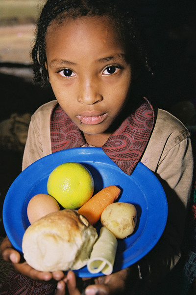 Ethiopian Jewish child with school lunch consisting of egg, potato, orange, bread, cheese, carrot and beans (not shown). The child who attends the Beta Israel School in Addis Ababa is one of about 4500 Ethiopian Students whose lunch is provided by the North American Conferance on Ethiopian Jewry (NACOEJ)